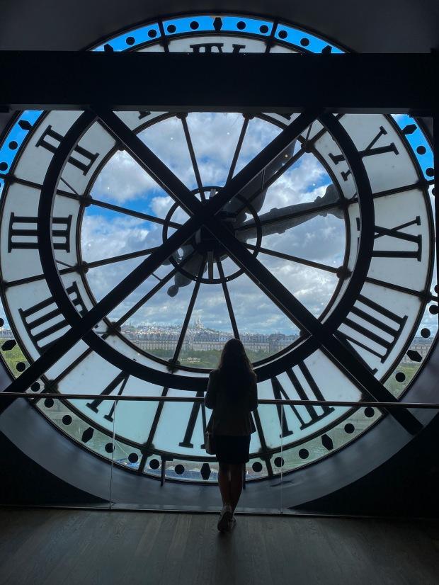 Mulher olhando a vista de Paris pelo enorme relógio de vidro do Museu D'Orsay